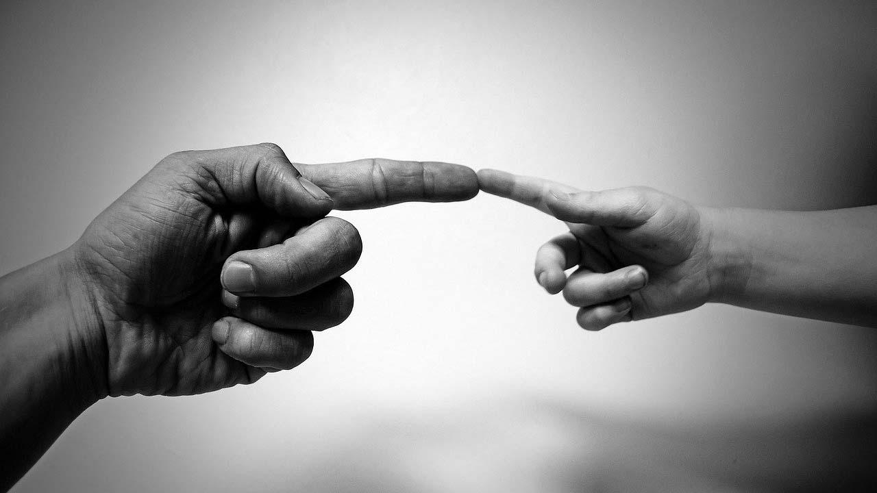 Image symbolique de deux mains qui se touche par l'index en hommage à l'oeuvre de Michel Angelo pour illustrer la communication de crise
